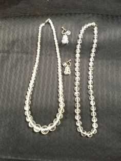 ART DECO ERA GROUPING OF HEAVY CRYSTAL NECKLACES AND ONE PAIR OF CRYSTAL DROP EARRINGS. BOTH NECKLACES HAVE STERLING CLASPS AND MEASURE 19 INCHES IN LENGTH. THE CRYSTALS ARE HEAVILY FACETED FOR OPTIMAL GLITZ. THE EARRINGS MEASURE ONE INCH AND HAVE FLAT CRYSTALS WHICH GRADUATE IN SIZE. GREAT LOT OF JEWELS.