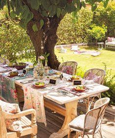 Comedor de exterior con vistas al jardín, suelo y muebles de madera y fibra vegetal, manteles vintage de flores 368067