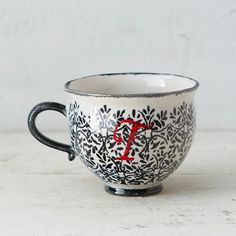 """A delicate vine motif sets off cherry red calligraphy on this personalized stoneware mug- Glazed stoneware- Dishwasher and microwave safe- Portugal3.75""""H, 4.5"""" diameter"""