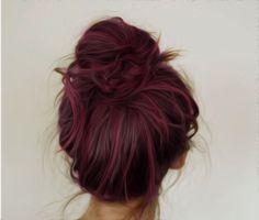 Redish purple hair in a messy bun.
