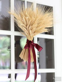 Looking for a last-minute way to add personality to your front door before those first holiday guests arrive? This quick trick will impress them at first knock. Gather a bunch of dried wheat and secure together in the center using a rubber band. Use scissors to trim ends to the same length, and finish with a thick silk or velvet ribbon.