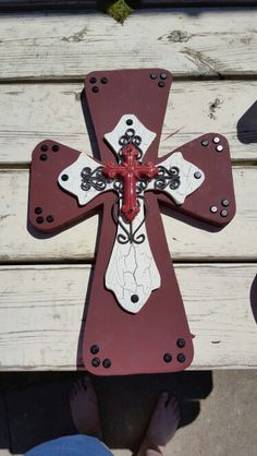 New cross design  This cross is 18 inches tall and 11.5 inches wide. The bottom layer is painted in maroon and with buttons around corners. The top cross is painted crackling white on top. The third cross is metal. All of my crosses are never alike.  It will have hanger on the back.