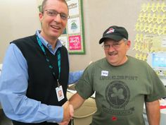 Donor services director Andrew Keelor gives Wendell Clark a congratulatory handshake for his 600th donation!
