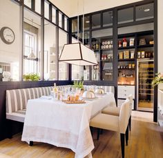 clever, cozy dining space.  dark windows banquette + planking + pendant