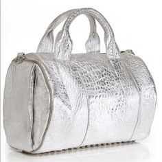 Pre loved Alexander Wang Rocco metallic silver bag Textured-leather (Lamb) Two top handles, detachable shoulder strap Zip side pocket, studded base, silver hardware Internal pouch and zipped pockets Fully lined in black  Zip fastening along top No dust bag or shoulder strap please see pics for signs of wear   InchesCentimeters Size	Width	Height	Depth	Min. Strap Length	Max. Strap Length	Handle Drop n/a	12.5	9	8.5	29.5	31	3.5 Alexander Wang Bags Crossbody Bags