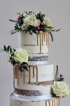 Semi naked drip wedding cake, a touch of glamour with gold chocolate drips, perfect for a relaxed wedding. Dressed with beautiful blooms and foliage. Cake and photo by The Confetti Cakery.