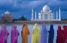 Women drape themselves in colorful sarees in front of the Taj Mahal. Travel India.