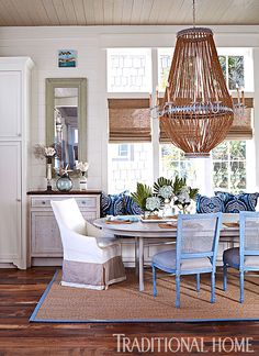 A built-in window seat combines with a mix of slipcovered armchairs and side chairs for a casual effect at the dining room table. - Photo: Jean Allsopp / Design: Georgia Carlee