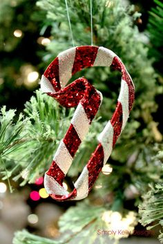 Cover candy cane shaped cookie cutter with glitter and wrap wuth white ribbon