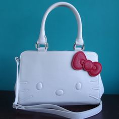 Sophisticated white handbag will add charm to any outfit. Comes with adjustable strap for crossbody wear, red 3D bow and black Loungefly logo lining. One of Lulabites favorites! Dont forget the watchi