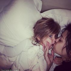 Doting mother: Kourtney Kardashian shared this adorable photo of herself kissing three-year-old daughter Penelope while laying in bed on Wednesday morning