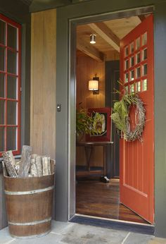 A wood bucket filled with logs at the front door adds a rustic, wintry touch to…