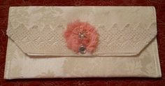 A handmade much simpler Ivory damask clutch bag. Made from Ivory Damask trimmed in vintage hand crocheted lace topped of with a handmade pink fabric flower wiht rhinestones. The clutch has a magnetic closure. Again room enough for cell phone, money and others extras. Measurement 12 x 7 All edges on the inside are well …