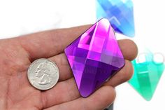 MAIN DETAILS:  Material: Acrylic Lead Free (Safe for skin, can be used as face gems) Size: 48x67mm or 2 x 2-1/2. Quantity: 2 Pieces Per Unit. Color: Purple Amethyst H105  Perfect for displays and visual arts. Add dimension and sparkle to any project with these fine quality acrylic gems. Square faceted, they are flat back with silver backing. These jewels are loose, without any glue or settings, making them great for event decorations and displays. Lead Free. CPSIA and RoHS compliant.  Yo...