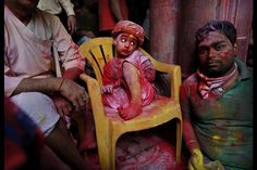 A young Hindu devotee sits covered in colored dye at the Banke Bihari temple, dedicated to Lord Krishna, during Holi festival celebrations in Vrindavan, India. Holi, the festival of colors, celebrates the arrival of spring.