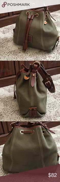 """Dooney and Bourke drawstring leather bag Dooney drawstring bag color,is olive green, no scratches on leather, some discoloration on bottom of bag ...I presume from use.  No stains or marks on inside of bag.  Measurements 10-1/2"""" wide, 10"""" high, 5"""" i. Depth, strap drop  is 11"""" and is adjustable to make shorter. Inside is lined in red with zip pocket on back wall, and small cell phone pocket on opposite.  Will not fit the new iPhones.  From a smoke free home,  dark brown trim, handle and…"""