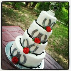Western Wedding - Simple Western wedding cake with fondant horsehoes, and red b/c roses.  The topper was provided by the bride.   TFL