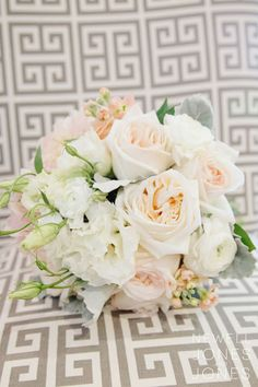 This dreamy bridal bouquet is composed of blush O'Hara garden roses, white ranunculus, white lisianthus, peach stock, and dusty miller. (Submitted by Painted Primrose Florist; Photo by Newell Jones & Jones Photography)