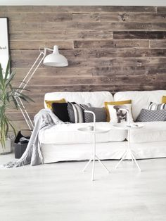 Our livingroom, wooden wall, pillows in couch, white floorlamp, hay tray tables