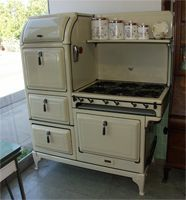 "This links to a wonderful site for antique and vintage stoves! From the 1930's, this Magic Chef features 6 burners, a double oven, warming oven, storage drawer, and shelf. It is cream colored with black trim, and come with a custom vent hood. It measures 53"" wide x 64"" tall."