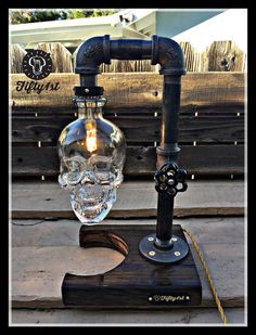 From Fifty1st comes another quality piece Max. This table lamp features a reclaimed wood base, steal pipe construction, a small yet powerful halogen bulb, stunning reclaimed Skull Vodka bottle and and a fully functional dimmer water valve switch! Features: • Reclaimed solid wood base • Steel pipe fittings • 40 watt Xeon halogen bulb (included) • 3/4 Brass water shut off valve dimmer on/off switch. • The bottle attaches with the use of magnets for easy bulb changes! Lamp Dimensions* Height…