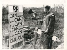 """1944- Soldier reading sign at 5th Army fuel dump in Italy which reads """"CAN you produce an empty CAN? If you CAN we CAN supply a full CAN...CAN for CAN""""."""