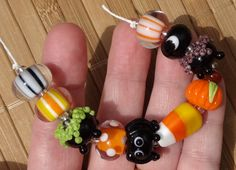This listing is for a set of 9 handmade lampwork beads. Beads included are; 1 black bead w/ crescent moons, 1 orange yellow and white striped bead encased in clear, 1 witches cauldron w/ purple bubbly goo, 1 orange bead encased in clear with white dots, 1 spider bead, 1 candy corn bead, 1 witches cauldron w/ green bubbly goo, 1 pumpkin bead, and 1 orange, white striped bead encased in clear, and 1 black and white striped bead.  Please see shop policies section for information on payment…