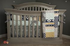 A gender-neutral tribal aztec nursery featuring all gray solid wood furniture with a slightly rustic/worn-looking finish.