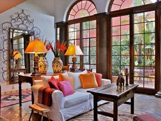 Traditional Meets Contemporary  From the terra-cotta tile flooring to the tall arched French doors, this living room is a contemporary twist on traditional Spanish design. The warm accent colors look crisp against the white walls and sofa. The living room's color scheme is carried through to the adjacent traditional Spanish-style courtyard. Design by Carole Meyer