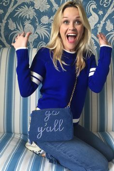 Reese Witherspoon wearing Saint Laurent Court Classic Star-Appliqued Leather Sneakers, Draper James Crop Flare Fringe Denim, Draper James Denim Go Y'All Clutch in Blue White and Draper James Tailgate Sweater