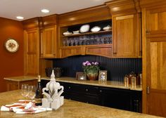 This gorgeous, traditional kitchen by David Stimmel features warm wood cabinets paired with neutral granite countertops. The lower cabinets are painted black to provide beautiful contrast and to complement the paneled backsplash.