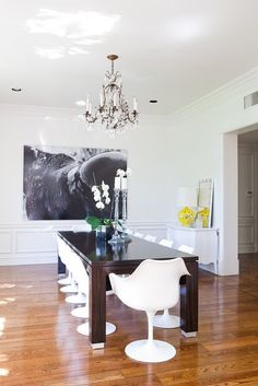 rachel zoe dining room, tulip chairs, dark wood lacquer table, close up of horse pic, white Bombay style buffet, all white walls and traditional chandelier. Love