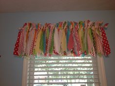 Curtain fun! Strips of fabric tied to a curtain rod with the ends snipped at different angles.