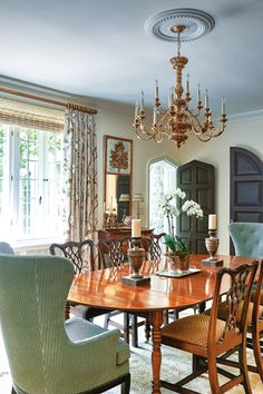 The #dining #room also leads outside through a Tudor-style arched door. Designed by Susan Beimler. #interiordesign #homedesign #elegantdesign