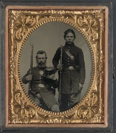 Two unidentified soldiers, possibly father and son, in Union uniforms and U.S. belt buckles with bayoneted muskets. Between 1861 - 1865.