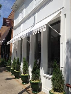 white awning + connifers. love the idea of incorporating plants into storefront design