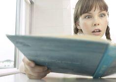 tyttö lukee kirjaa hämmästyneenä