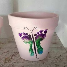 Plant pot decorated with child's feet in a butterfly pattern