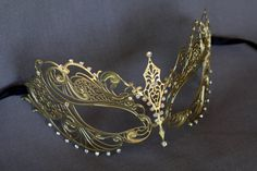 This id gorgeous gold masquerade mask that I added to the large variety of different designs of metal masks and lace embroidered masks. This mask is a metal mask decorated with shimmered rhinestones to enhance the design of the mask and the facial features! hope you love this mask!  If this is not the mask you were looking for please take a look at my other mask that I have in my shop also contact me if you wish any changes in any of my items at my shop. I can make that item to match your…