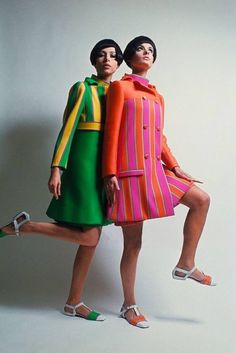 Two models stand together wearing fashions by Ungaro; at left, model wears a bright green coat, with Empire bodice of yellow and green stripes, trimmed in purple, a matching green dress beneath; model at right wears a pink and. 60s Fashion Trends, 60s And 70s Fashion, Retro Fashion, Vintage Fashion, Sporty Fashion, Style Fashion, Gothic Fashion, Fashion Outfits, Estilo Mod