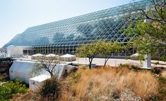https://flic.kr/p/7eqXmf | side view, Biosphere 2 (1990), Oracle, Arizona | contains tropical rain forest, desert, savannah, and cloud forest ecosystems, also a miniature ocean with a coral reef • 3.14 acres • 6,500 windows • 91 ft. at highest point • sealed below by 500-ton welded stainless steel liner • campus is 40 acres  Biosphere 2 designed as completely closed ecological system to research interactions within ecosystems and possibility of colonization of space • $200 million for…