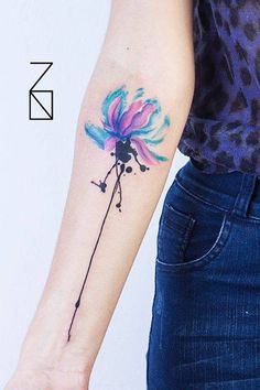 Watercolor style lotus flower tattoo on the right forearm.