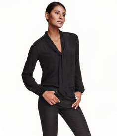 Loose-fitting, long-sleeved blouse in airy, woven viscose fabric. V-neck with tie, elasticized cuffs, and gently rounded hem.