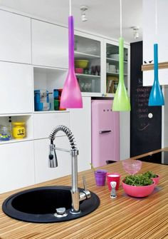MIESZKANIE. W biało-czarnej kuchni wzrok przyciąga różowa lodówka, błękitny ekspres do kawy, żółta waga kuchenna z Legolandu, kolorowe lampy...