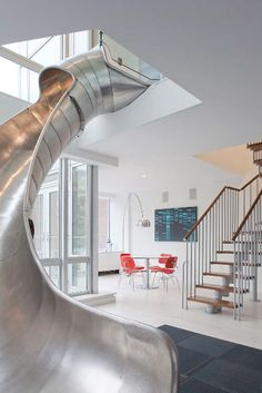 NYC Home with a Steel Slide by Turett Collaborative Architects. Connecting smaller apartments together into a seamless whole in the East Village.