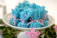 Trouxinhas feitas de tecido floral azul e rosa foram recheadas com trufas para serem servidas aos convidados.