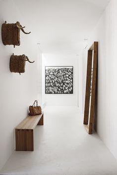 Buena entrada - AD España, © Belén Imaz En la entrada, banco de roble creado por los arquitectos suizos; espejo, en Batavia; cabezas de toro de Javier Sánchez Medina y pintura de Renée-Mireille Héaulmé.