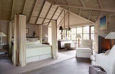 Quarto com cama de casal e pequena salinha, sem divisão para a casa de banho.