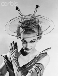 1956: Juli Dane modeling a futuristic hat, for brides a thousand years from now, at a Boston fashion show. It's from the famed Golden Wedding collection of bridal gowns and accessories of the past, present and future. The dual antennas and headset are supposed to let the young bride, honeymooning on the moon, keep in touch with family and friends on earth.