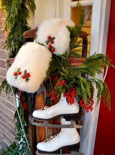 A DIY porch decor using an old sled, hand muffs, ice skates, green holly and red holly berries. A delight that brings back memories of my childhood!  I always wanted a hand muff as a little girl.
